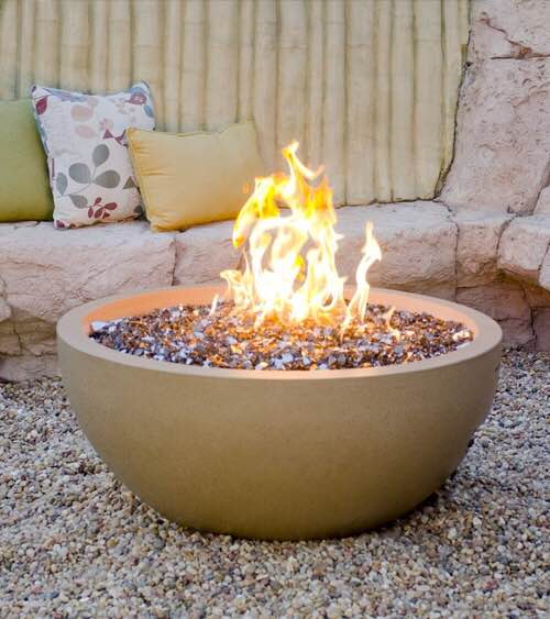Custom Firepit burning with stone seating and pillows in the background.