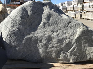 A large grey landscape boulder sitting in the sun