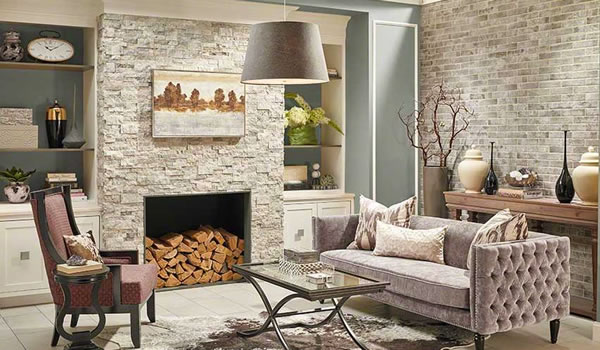 A picture an inside fireplace with a stone veneer.